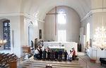 Toinen kuva ehtoollisen jakamisesta Kirkkonummen Pyhän Mikaelin kirkon alttarikaiteen ääressä.