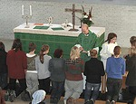 Kuva ehtoollisen jakamisesta Kirkkonummen Pyhän Mikaelin kirkon alttarikaiteen ääressä.